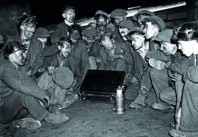 Coal miners sitting around radio in briefcase