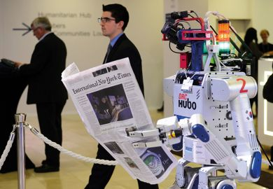 A robot holds a newspaper during a demonstration at the World Economic Forum (WEF) annual meeting in Davos