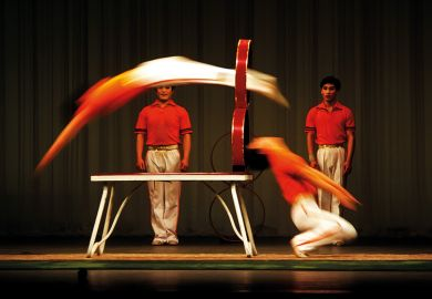 Acrobats jumping through hoops