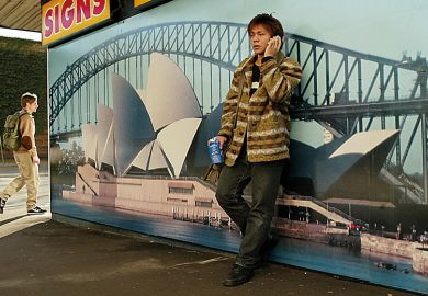 Asian student leaning against picture of Sydney Opera House, Australia
