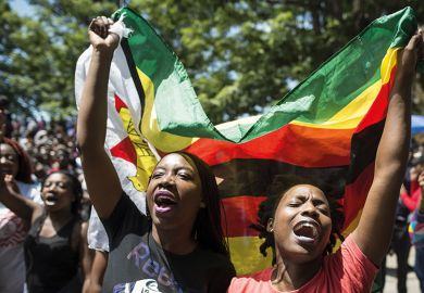 Women holding a flag of Zimbabwe in a demonstration at the University of Zimbabwe