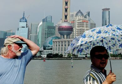 People walk along the Bund in front of the skyline of the city's financial district of Pudong, in Shanghai