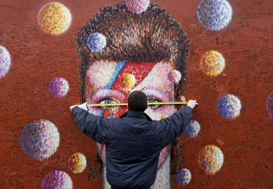A workman measures up a mural of British musician David Bowie in Brixton, south London