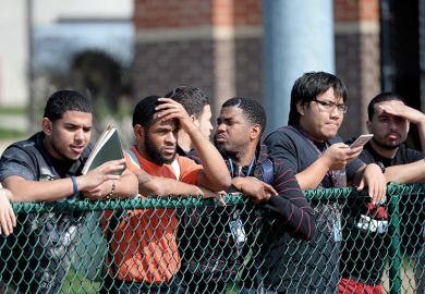 Students line the fence at the football field at university, USA