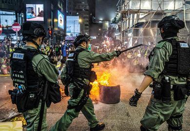 Police stand guard on a road to deter pro-democracy protesters from blocking roads in the Mong Kok district of Hong Kong on May 27, 2020, as the citys legislature debates over a law that bans insulting China's national anthem.