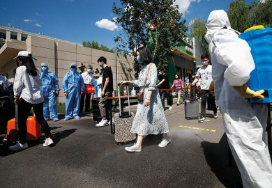 Teachers wearing face masks take part in a drill at Beijing University of Chemical Technology on May 27, 2020 in Beijing, China. The university carried out an epidemic prevention and control drill on Wednesday in preparation for its reopening.