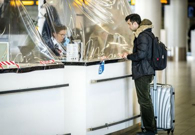 A passenger stands at an airline counter protected with a plastic tarpaulin on March 27, 2020, Netherlands