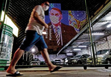An image of Brazil's President Jair Bolsonaro wearing a protective face mask and the phrase Hysteria Damages the Economy is projected on the wall of a building as a protest against the president regarding his handling of the coronavirus COVID-19 outbreak