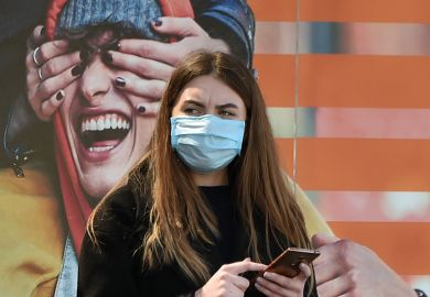 A woman wearing a face mask stands by an advertising placard showing someone having their eyes covered, April 21, 2020