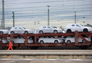 New Audi AG automobiles, manufactured by Volkswagen AG, sit under protective covers on a railway transporter beside a platform at Ingolstadt central train station in Ingolstadt, Germany