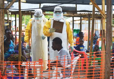 An MSF medical worker, wearing protective clothing relays patient details and updates behind a barrier to a colleague at an MSF facility in Kailahun, 2014. Kailahun along with Kenama district is at the epicentre of the world's worst Ebola outbreak
