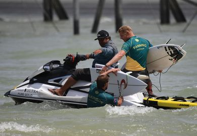 Mick Fanning of Australia (R) helps teammate Matt Wilkinson with his broken board during the qualifiers for the final of the WSL Founders' Cup of Surfing