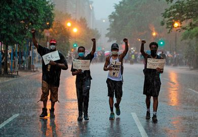 People holds signs as they walk in the rain after attending a Black Lives Matter protest in front of Lafayette Park next to the White House, Washington, DC on June 5, 2020
