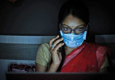 Young Indian Woman wearing mask working on her laptop and talking on phone