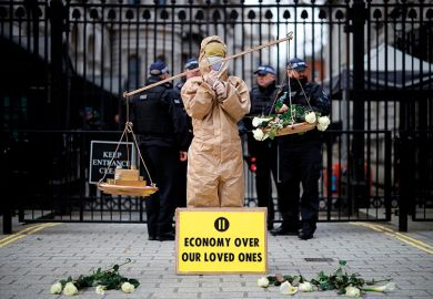 "A protester from the group ""Pause The System"" stands beside the entrance to Downing Street in central London on March 17, 2020."