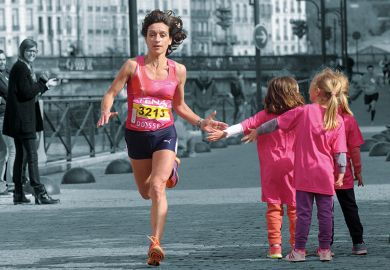 A female runner giving children a high five as she runs past.