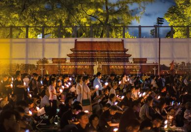 People hold candles in front of a backdrop showing  Beijing's Tiananmen Square during a vigil in Hong Kong on June 4, 2018