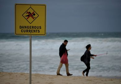 Visitors walk on Bondi beach next to a warning sign for dangerous sea currents on a stormy day in Sydney