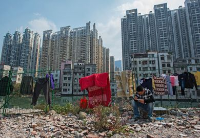 A man sits on a rock near demolished residential buildings in Xiancun, an urban village in the Zhujiang New Town district of Guangzhou as high commercial and residential buildings rise in the distance