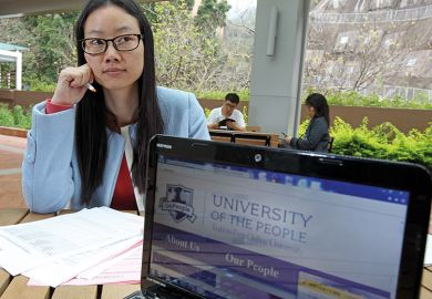 Woman poses with the website of the University of the People in Pok Fu Lam