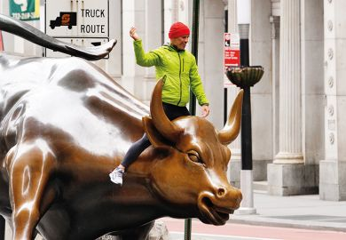 A person can be seen riding the Charging Bull in the financial distrcict  of New York City amid Coronavirus pandemic on April 5, 2020.