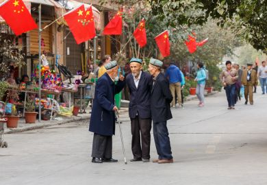 KASHGAR, XINJIANG / China - October 4, 2017: Three elderly men of the Uyghur minority having a conversation at a street in Kashgar Old Town. Chinese flags are mounted on the house in the background.