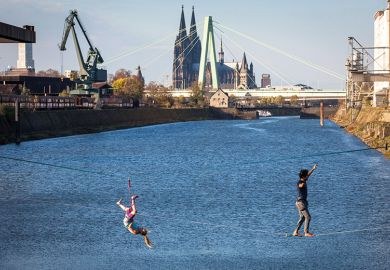 man and woman on slacklines in the Rhine harbour in Deutz, with the cathedral and Severins bridge in the background, Cologne, Germany, as a metaphor for European universities balancing cost and ambition