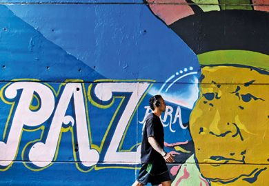 Man walking past paz graffiti in Colombia