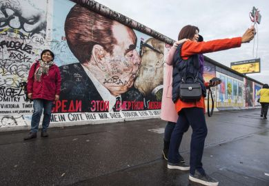 Tourists pose in front of Dmitri Vrubel mural, Berlin Wall