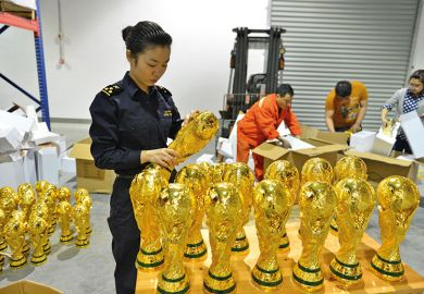 A woman standing over a box of football trophies