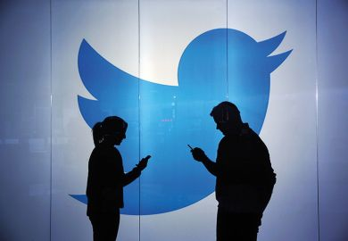 Two people silhouetted against Twitter logo