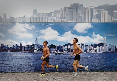 Two men jog past a billboard featuring photos of the city skyline with a clear sky on a cloudy day in Hong Kong