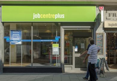 Two men walking past the Job Centre Plus government employment office in the centre of Weston-Super-Mare