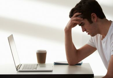 Unhappy male student looking at laptop