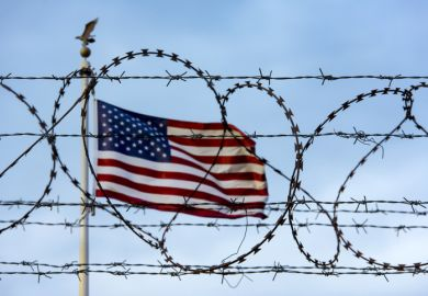 US flag behind barbed wire symbolising restrictions on international students coming to the US