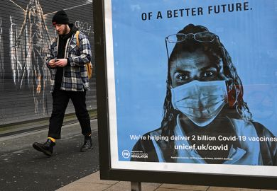 A pedestrian walks past a Unicef poster promoting Covid-19 vaccines, in Manchester, January 5, 2021, illustrating vaccine passports for campuses