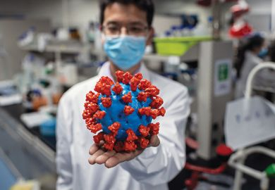 Scientist with model of coronavirus