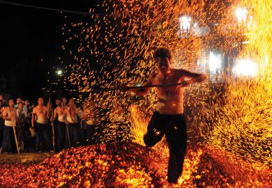 A man walking over burning coals