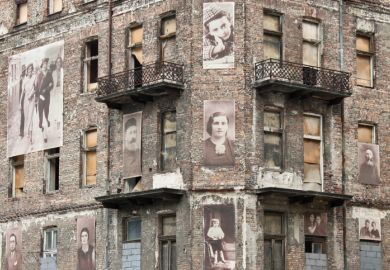 Warsaw, Poland - September 1, 2012 Holocaust memorial - a building from Warsaw ghetto with pictures of jews on the facade.