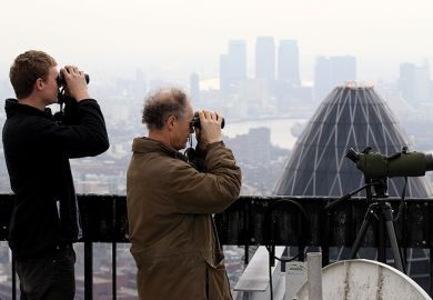 Birdwatchers use binoculars to observe birds from the top of Tower 42, London, illustrating UK institutions seeking to hire EU professors and postdocs