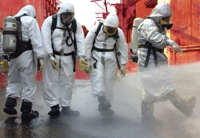 People in protective gear spraying water