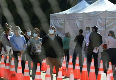 People wait in long lines for coronavius tests at a walk-up Covid-19 testing site