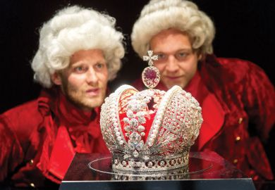 Two men in costume look at the model of the great tsars crown of the Russian Empire at the Hermitage in Amsterdam