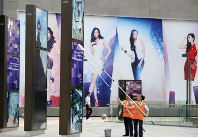 Two workers clean billboards outside a shopping mall in Beijing
