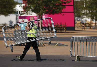 Workmen move barriers from outside the Olympic Stadium in Stratford