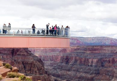 People standing on the The Skywalk on cantilever bridge in Arizona near the Colorado River