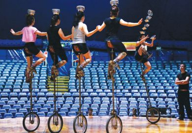 five people on unicycles balancing bowls on their heads with one toppling down as a metaphor for enrolments uncertainty in Australian Universities