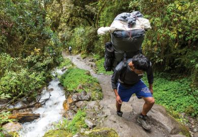 Hiker carrying enormous load on his back in the forest as a metaphor on the inexcusable fees levied on doctoral students.