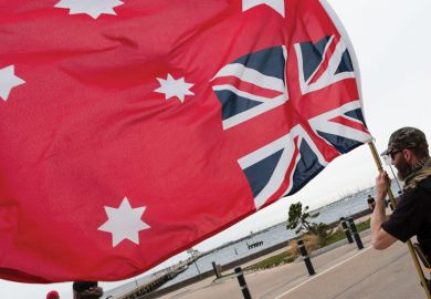 Person holding an upside down Red Ensign flag in Australia as a metaphor that legal academics say 'Top-down' rules won't solve free speech fears.