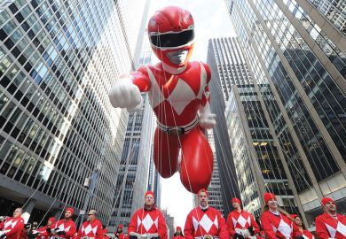 Giant inflatable Power Rangerheld by people walking behin as a metaphor for Alumni-led boards 'key to US universities' strength'